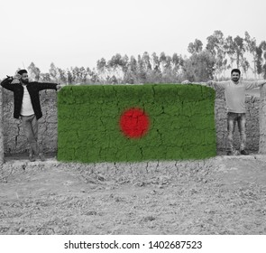 Two men standing around a Bangladeshi flag textures on a clay made surface