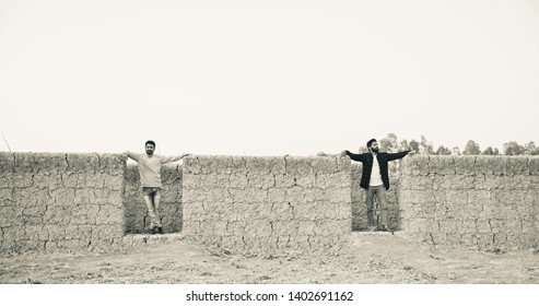 Two men standing around an incomplete clay made house