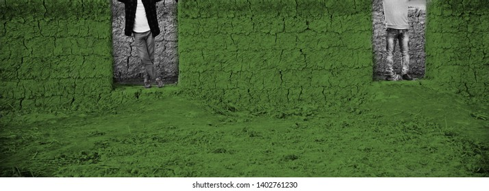 Two men standing at the door of a green clay made house