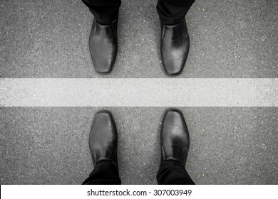 Two men standing on both side of the white line