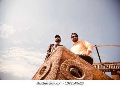 Two men standing on an old metallic boat unique photo