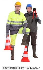 Two men stood with traffic cones