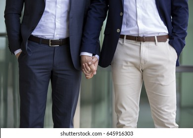 two men in suits standing and holding hands