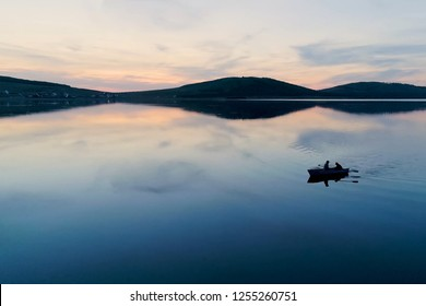 Two men swim in a boat on the lake against the backdrop of sunset
