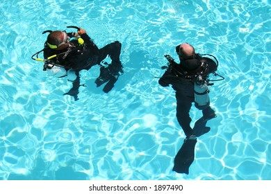 Two men take scuba diving lessons in a pool.