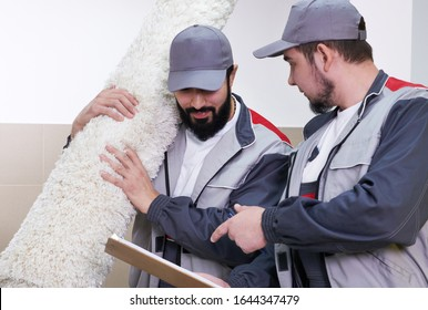 Two men taking away big carpet for cleaning service
