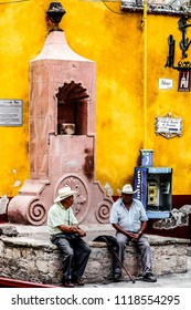Two men talking quietly at the street. San Miguel de Allende. June 2015, Mexico.