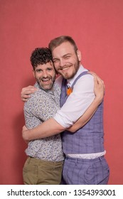 two men together, hugging gay couple, looking directly to camera. candidly smiling.
