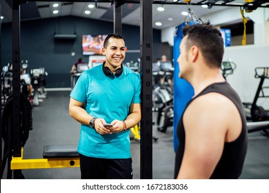 Two men training in gym looking at mobile phone