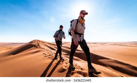 Two men trekking the Wahiba deserts in Oman.