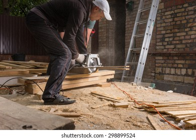 Two Men Using Hand Held Power Saw to Cut Planks of Wood for Home Construction Leaving Piles of Saw Dust on Floor