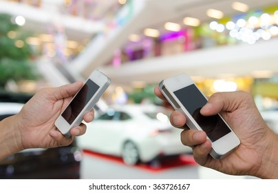 Two men using mobile smart phone with blurred background of new cars displayed in showroom, communication concept, transaction concept.