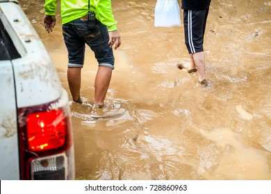 Two men are wading through the water to distribute clean drinking water. Thailand flood victims