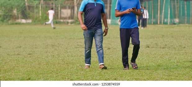 Two men walking in a sports ground unique photo