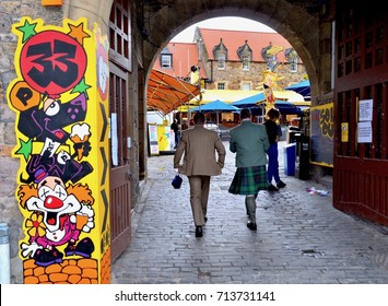 Two men walking through archway at entrance to Pleasance. Edinburgh fringe festival. August 2017. Scotland UK