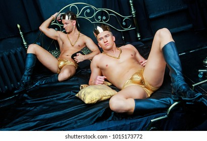 two men wearing golden underwear and  jewelry   in bed with black linen