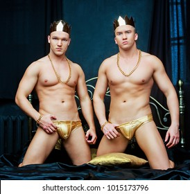 two men wearing golden underwear , crowns and  jewelry   in bed with black linen