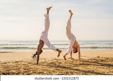 Two men in white pants practicing capoeira (brazilian martial art that combines elements of dance, acrobatics and music) on the beach