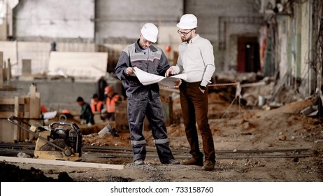Two men in white safety helmets are standing together in construction area with working people in the background and looking at scheme of design for future building.