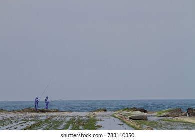 Two men who stands on the coast frontier of the washboard shaped tidal flat is fishing with the broad background of sky and ocean. The seascape of Yilan County, northeastern coast in Taiwan.