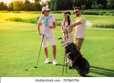 Two men and a woman are choosing golf clubs, talking and smiling while standing on golf course