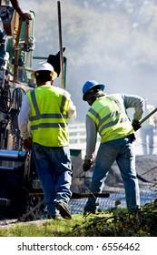 Two men working alongside an asphalt paving machine.