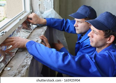 Two men in working clothes places the foiled insulation on the window sill