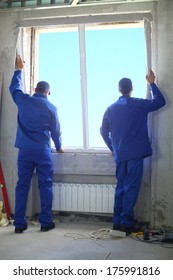 Two men in working clothes set new window frame into the window opening