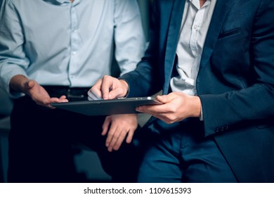 Two men working with touchpad. Cropped picture of two male office colleagues formaly dressed using touchpad to view presentation sitting in office.