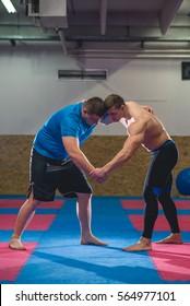 Two men wrestle in a training room