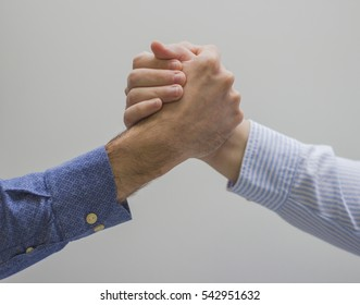 Two men's hands holding each other strongly.