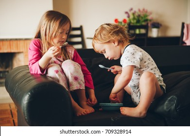 Two messy kids eating from one plate resting on the couch