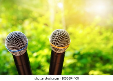 two metal black microphone for speech or communication in green nature sunlight environmental background