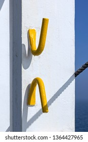 Two metal hooks on a wall on a ship. A rope casts a shadow. In the background you can see the ocean and the sky, all in blue.