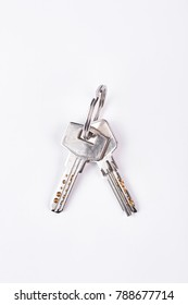 Two metal keys on ring. Pair of nickel door keys isolated on white background, top view. Two house keys on keyring.