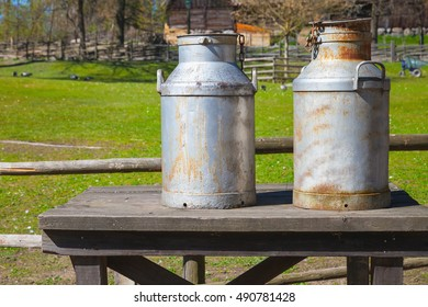 Two metal milk churns stand on wooden table