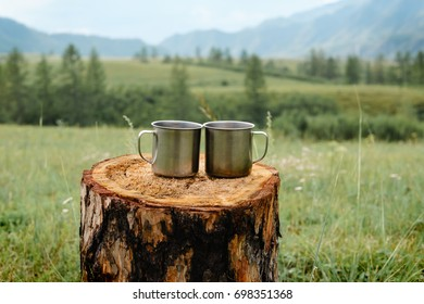 Two metal mugs on a wooden stump on a background of mountains.