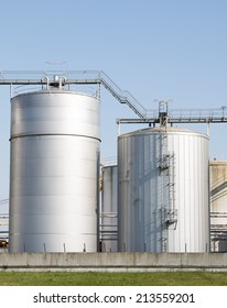 Two metal silos with stairs for food and agriculture on sky and green