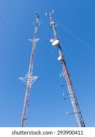 Two metal truss communication towers with various telecommunication antenna equipment, against clear blue sky, shot from low-angle
