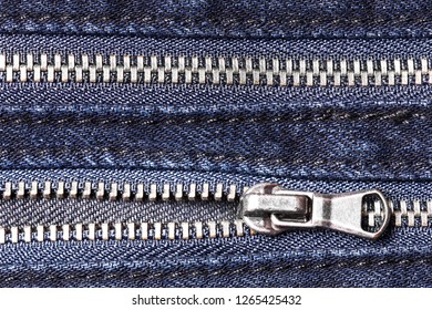 Two metal zippers in jeans trousers. Fashion fabric background texture.