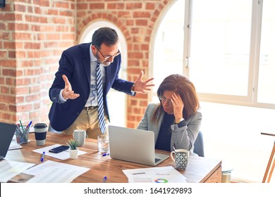 Two middle age business workers working together. Man bullying woman at the office