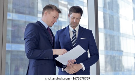 Two Middle Aged Businessmen Discussing Business Repor