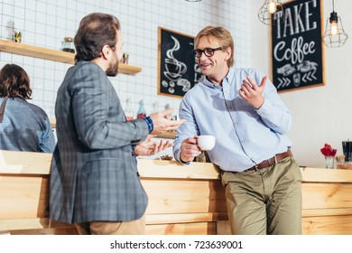 two middle aged businessmen drinking coffee and talking in cafe