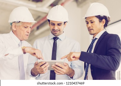 Two middle aged men in formalwear and hard hat showing something to smiling partner on tablet. Two architects presenting project to customer in digital form. Building and presentation concept