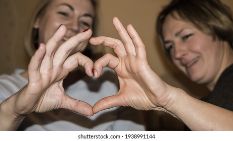 two middle aged women holding their hands in front of the camera making a heart shape with their fingers together