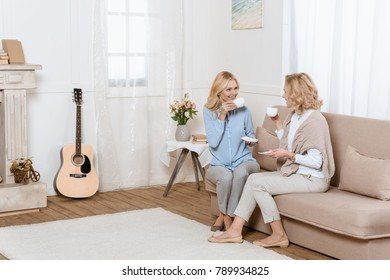 Two middle aged women sitting on sofa and drinking tea