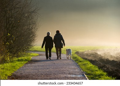 Two middle aged women walking a dog on a path in a park.
