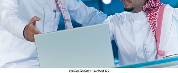 Two middle eastern businessmen at desk working on a laptop