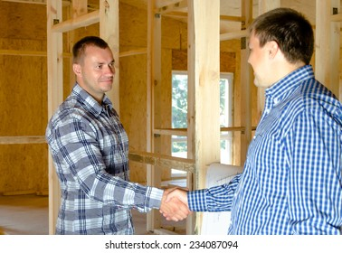 Two middle-aged men standing shaking hands in a new build incomplete timber frame house interior in a conceptual image of ownership, partnership or two professionals allied to the building industry