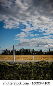 Two mile / kilometer posts on both sides of a summer asphalt road under a cloudy blue sky and a golden wheat field with a forest in the background